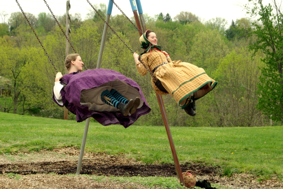 two women in antebellum dress on the swings